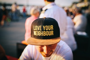 Man with love your neighbour on his hat