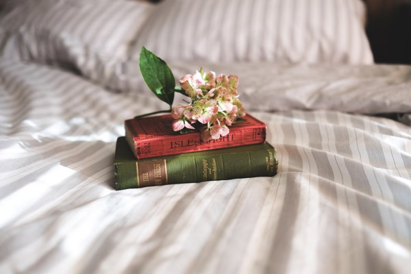 books on a bed with flowers