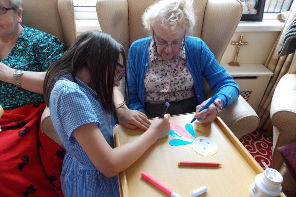 School girl and care home resident working on art