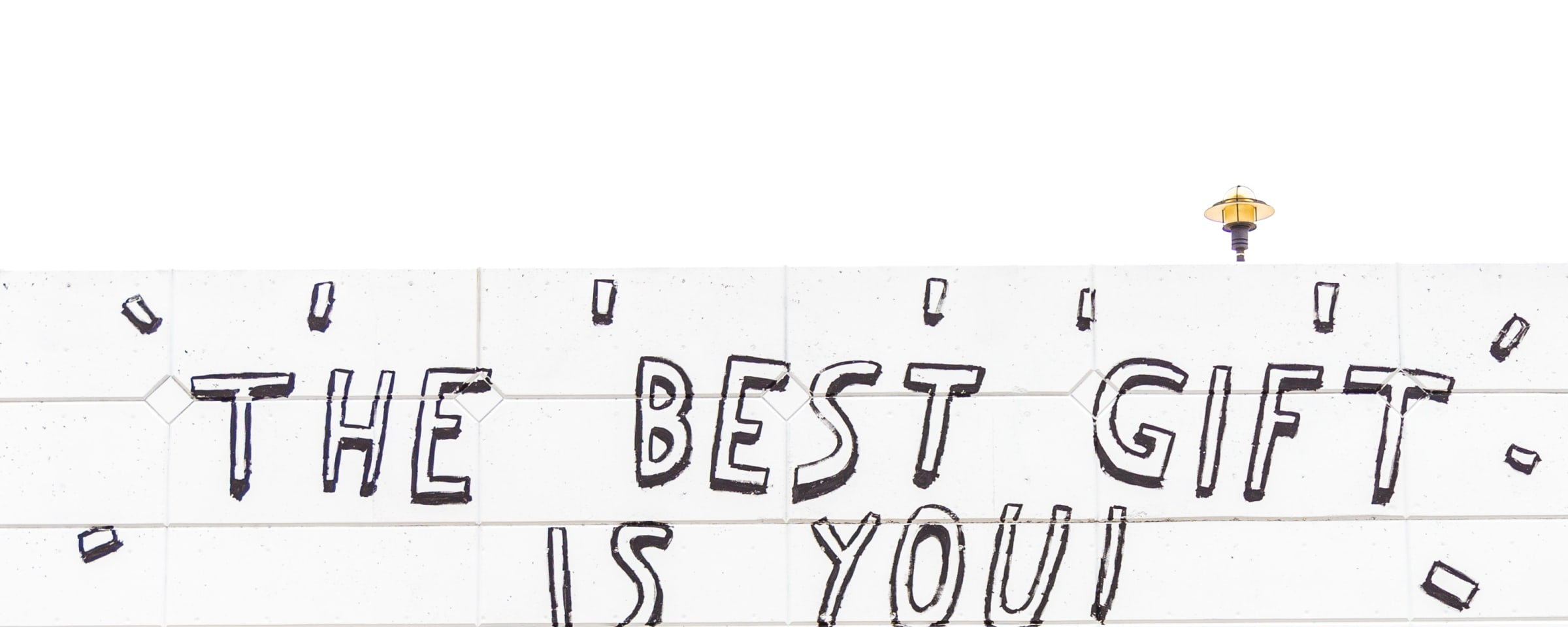 Woman walking by mural that says the best gift is you